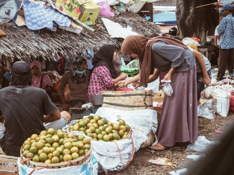Travel Itinerary for a day trip to Lombok - a local women choosing produce at Ampenan Market